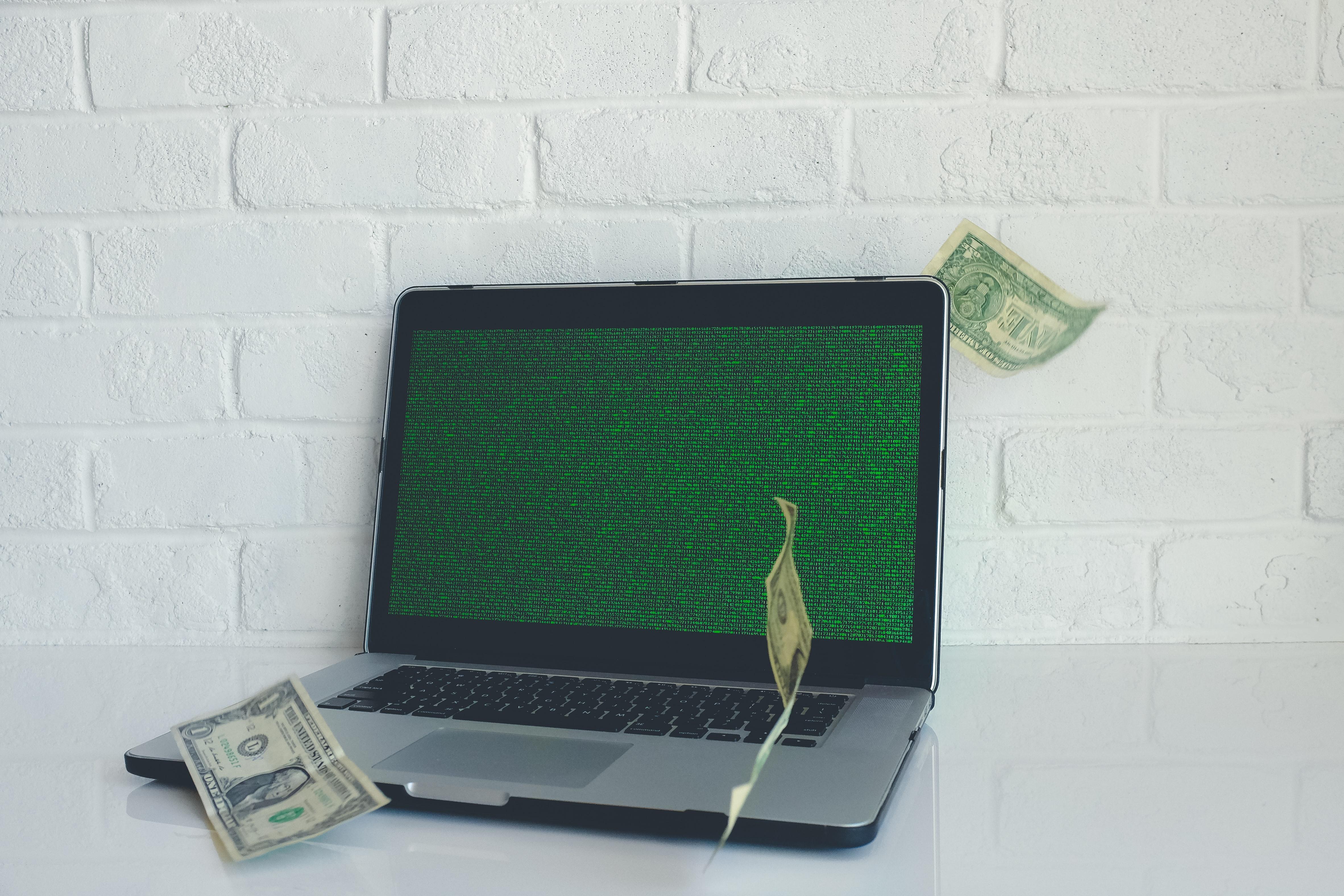 A macbook pro laptop with dollar bills falling on it