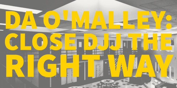 """A photo of Alameda County Juvenile Detention Facility in black and white. On top of the photo it says """"DA O'MALLEY CLOSE DJJ THE RIGHT WAY"""" in bold yellow lettering."""
