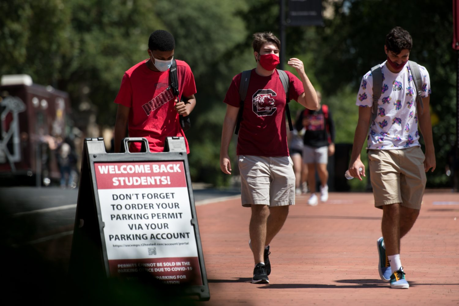"""Three university students with backpacks and masks on pass outdoor sign that says """"WELCOME BACK STUDENTS"""""""