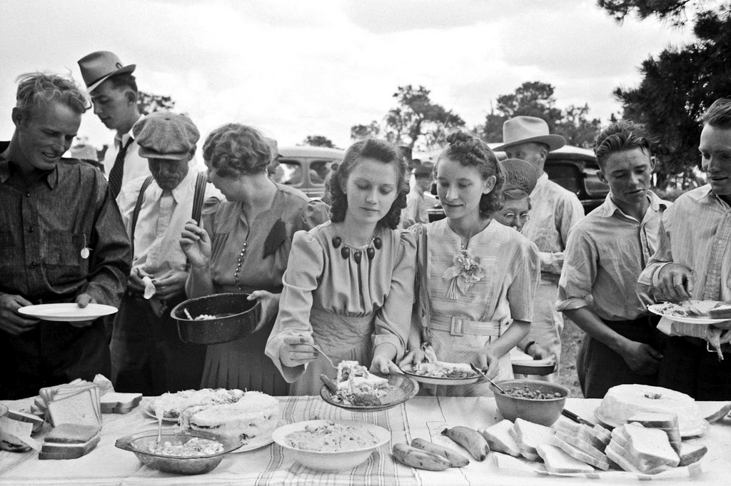Heaping the plates at dinner on the grounds, all day community sing. Pie Town, New Mexico, 1940