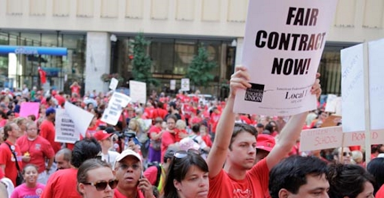 """Photo of a crowded downtown rally. One young person holds a sign at the front saying, """"Fair Contract Now!"""""""
