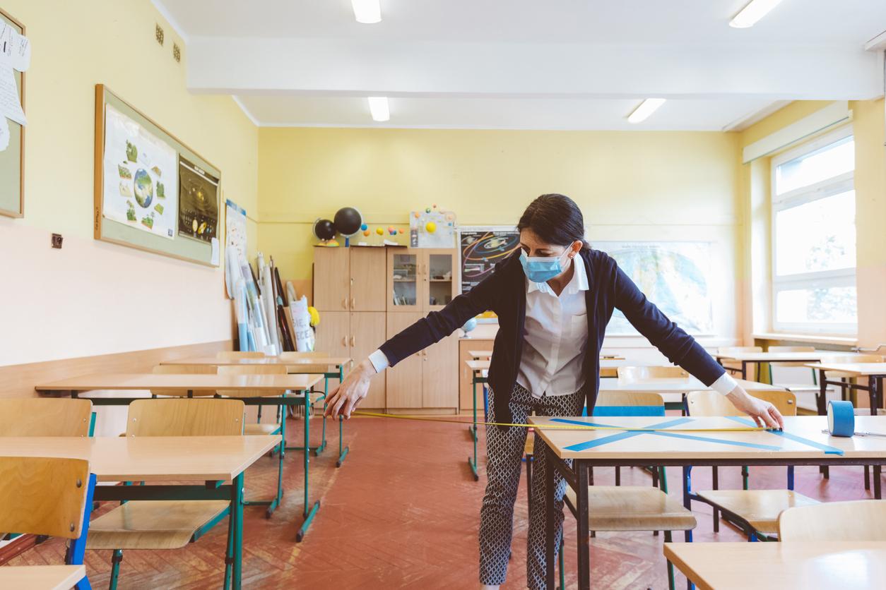 Masked teacher cleaning class