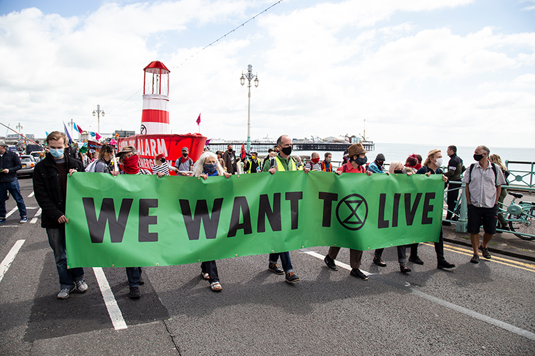 marchers with banner 'we want to live'