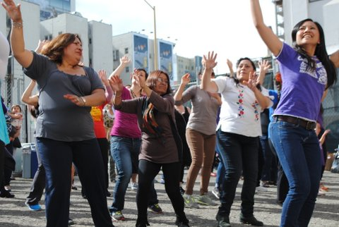 Image of Latina women in the streets with hands in the air dancing