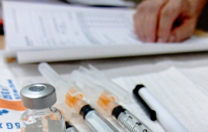 syringes lined. up next to vaccine bottle