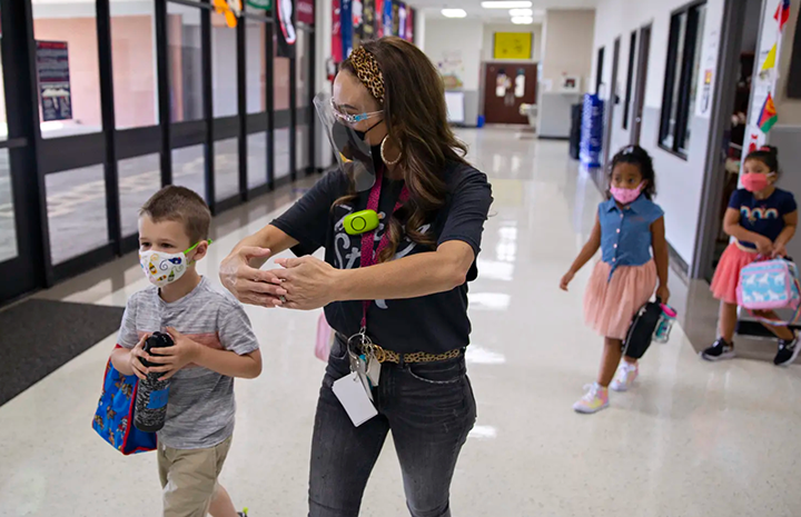 Masked teacher and young students walking down a campus hallway