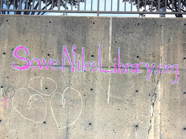 A message written in chalk on a wall that reads Save Niles Library .org.