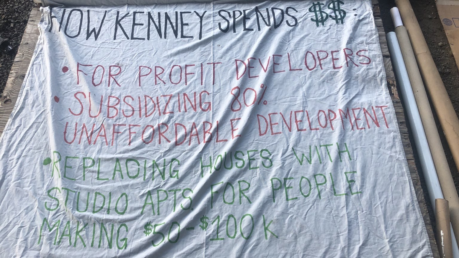 """Sign painted on a sheet that reads: """"How Kenney Spends $$: * For Profit Developers. * Subsidizing 80% Unaffordable Development. * Replacing Houses with Studio Apartments for People Making $50 - 100K"""