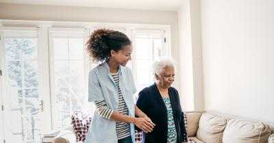 Home health aide assisting an elderly person