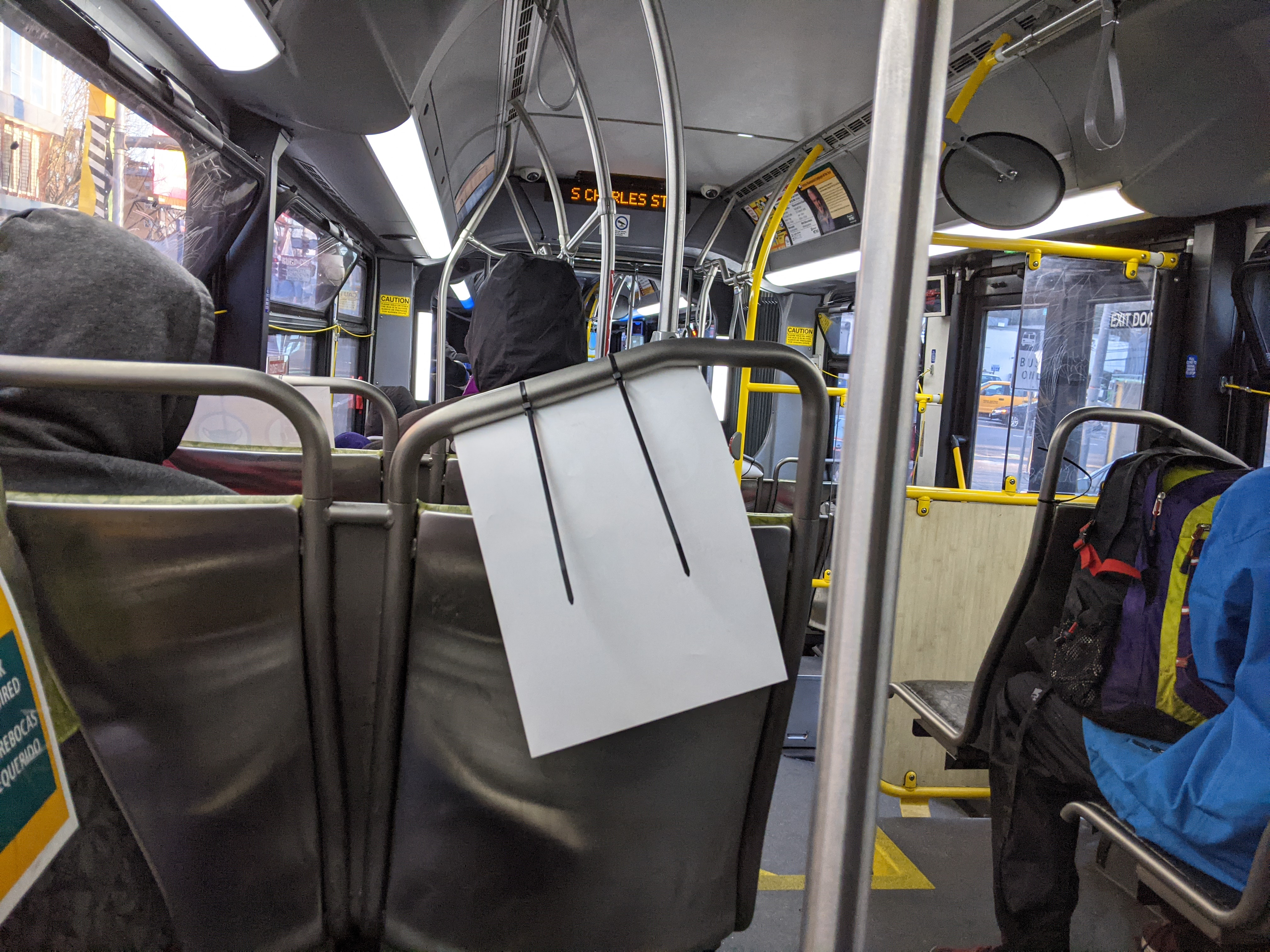 View from a seat on a bus. People sitting in seats in front are wearing hoods.